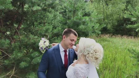 mariposa : Very beautiful bride and groom hold hands and hug in the forest. Archivo de Video