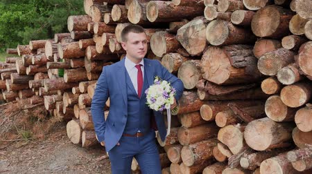 жених : Handsome groom in a jacket and with a bouquet stands near a pile of logs.
