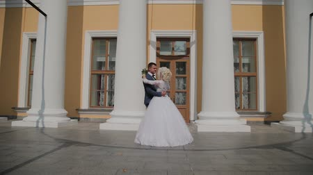 gracefully : Happy newlyweds dance their dance at the columns in the park. Stock Footage