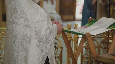 communion : An old priest stands at the altar and reads a prayer.