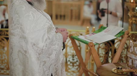 baptism : An old priest stands at the altar and reads a prayer.