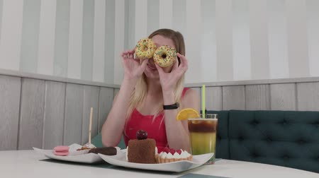 doughnut : Beautiful girl posing with donuts in hands at a table in a cafe.