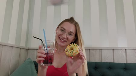 retro girl : Beautiful young girl dancing with a drink and a donut in hands while sitting at a table in a restaurant. Stock Footage