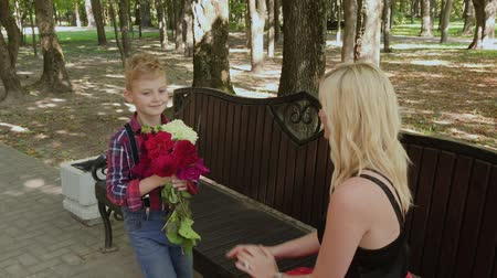 amado : Beautiful little boy gives a bouquet of flowers to his beloved mother in the park on a bench.