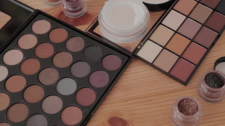 aplikatör : Professional makeup kit in a makeup studio on a wooden table. Stok Video