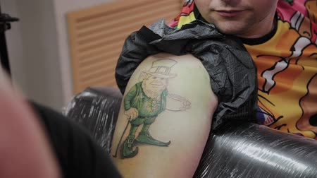 adorno : Professional tattoo artist makes a tattoo on a man s arm. Vídeos