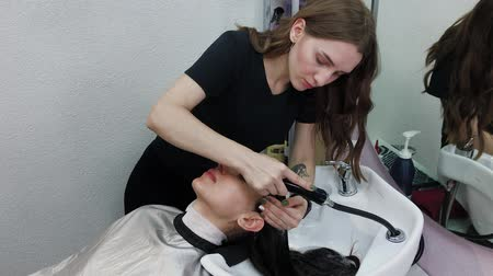 kartáč na vlasy : Beautiful young girl wash their hair at the hairdresser. Dostupné videozáznamy
