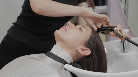 şampuan : Beautiful young girl wash their hair at the hairdresser. Stok Video