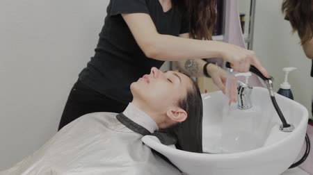 barber scissors : Beautiful young girl wash their hair at the hairdresser. Stock Footage