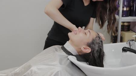 コンディショナー : Girl hairdresser puts shampoo on the head of a client.