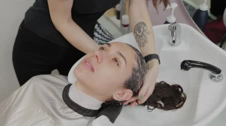 meia idade : Girl hairdresser puts shampoo on the head of a client.