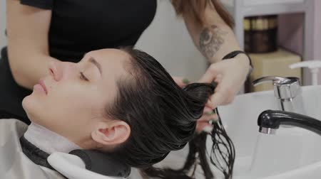 barber equipment : Beautiful young girl wash their hair at the hairdresser. Stock Footage