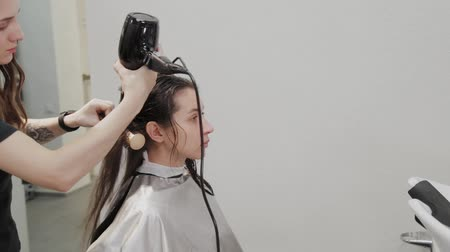 kartáč na vlasy : Girl hairdresser dries hair to client with hairdryer at hairdresser. Dostupné videozáznamy