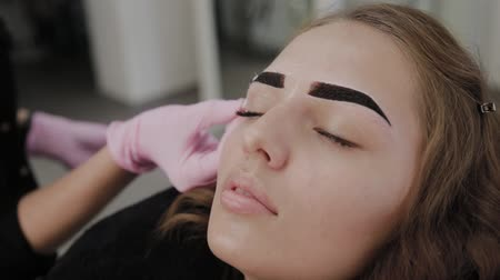 kaşları : Professional makeup artist paints eyebrows to client with henna. Stok Video