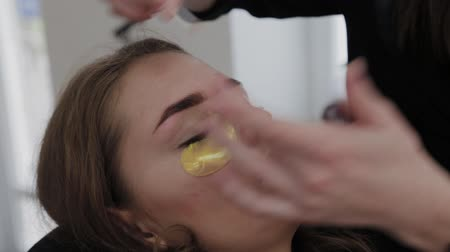 щетка для волос : Professional makeup artist removes eyebrow paint to client.