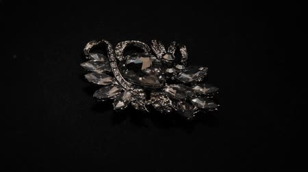 spilla : Brooch in with stones on a black rotating stand. Premium Jewelery. Macro.