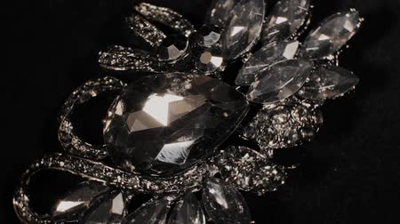 drahokamy : Brooch in with stones on a black rotating stand. Premium Jewelery. Macro.
