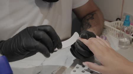 żel : Professional manicurist man polishes and smoothes girls nails with a nail file. Wideo