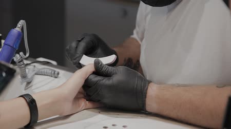 cuticle : Professional manicurist man polishes and smoothes girls nails with a nail file. Stock Footage