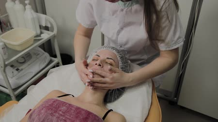 towel white : Woman doing facial massage at the spa salon. Stock Footage