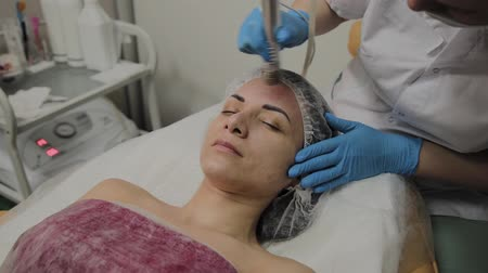 clay mask : A professional cosmetologist makes a woman vacuum cleaning the face in a beauty salon. Cosmetological innovations. Stock Footage