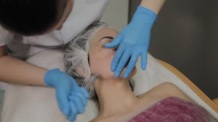 eye mask : A professional cosmetologist makes a woman vacuum cleaning the face in a beauty salon. Cosmetological innovations. Stock Footage