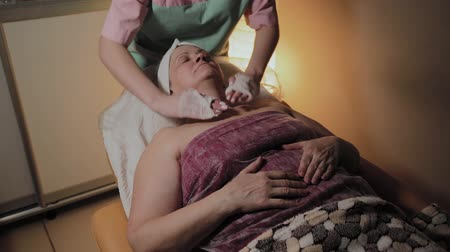 arcszín : A professional beautician prepares the face of an elderly woman for the procedure. Cosmetological innovations