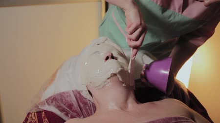 collagen : A professional cosmetologist applies a face mask to an elderly woman. Cosmetological innovations. Stock Footage