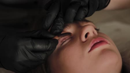 divisione : A very beautiful girl in a beauty salon does a lamination lashes. Beautician performs the procedure eyelash fragmentation.