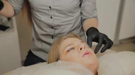 folt : A very beautiful girl in a beauty salon does a lamination lashes. Beautician performs the procedure eyelash fragmentation.