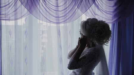 серьги : Beautiful bride closes earrings by the window. Стоковые видеозаписи
