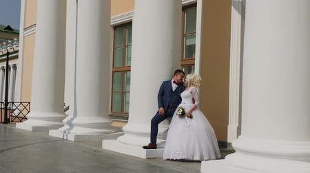gracefully : Happy newlyweds stand at the columns in the park.