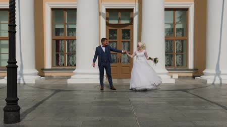 chique : Happy newlyweds dance their dance at the columns in the park. Vídeos