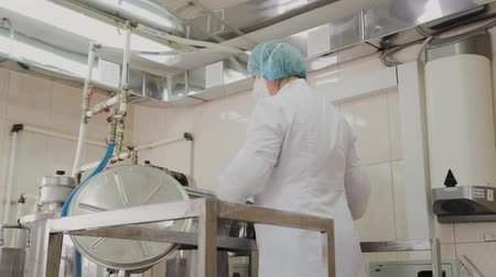 biomassa : Female scientist puts ingredients into the reactor for the preparation of medicines.