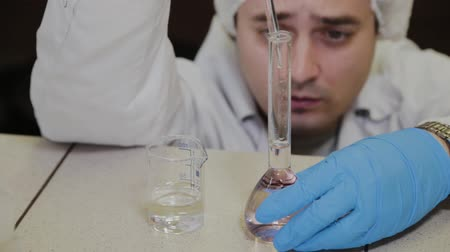 biotechnologia : Male scientist with test tubes in a laboratory conducts an experiment.