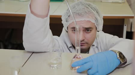 cientista : Male scientist with test tubes in a laboratory conducts an experiment.