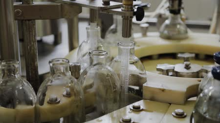 üreten : Pouring medicine on an assembly line into glass bottles for injection.