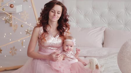 Beautiful mother with a one-year-old daughter in beautiful dresses and New Years decor. New Year 2020.