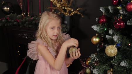dez : A ten-year-old girl near the New Year tree holds a New Year s toy in her hands. New Year 2020. Vídeos