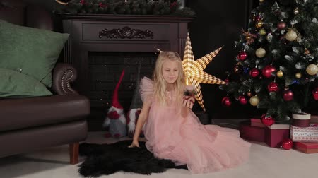 s : A ten-year-old girl near the New Year tree holds a New Year s toy in her hands. New Year 2020. Stockvideo
