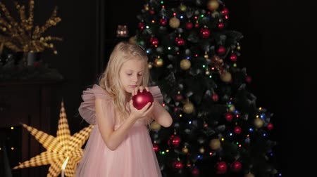 десять : A ten-year-old girl near the New Year tree holds a New Year s toy in her hands. New Year 2020. Стоковые видеозаписи