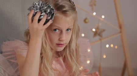 devět : A nine-year-old girl in New Year s decor holds a New Year s toy in her hands. New Year 2020. Dostupné videozáznamy