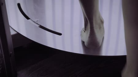 A woman walks into a solarium, legs closeup.