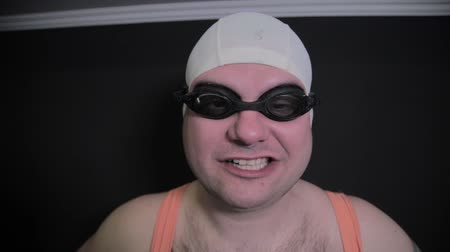 nadador : A man in a swimming cap and goggles.