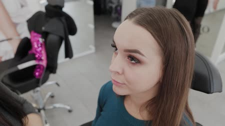 Professional makeup artist woman paints eyelashes to client of beauty salon. Vídeos