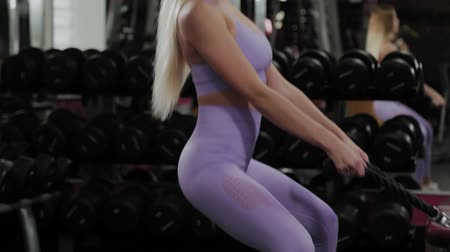 kaldırma : Athletic woman with a beautiful figure trains legs and buttocks on a block simulator in a gym. Stok Video