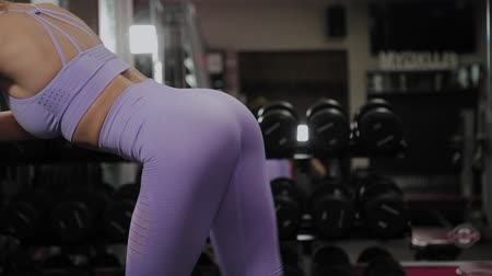 bil : Athletic woman with a beautiful figure trains the buttocks on a block simulator in the gym.