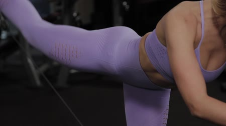 legginsy : Athletic woman with a beautiful figure trains the buttocks on a block simulator in the gym.