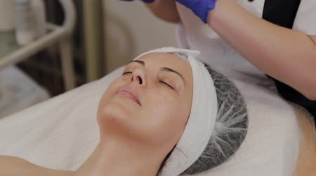professional wellness : Professional beautician wipes woman face with wet wipes. Stock Footage