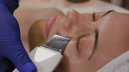 zmarszczki : Professional beautician does ultrasonic face cleaning for middle-aged woman. Wideo